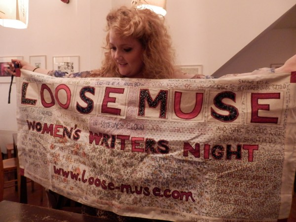 Sara-Mae Tuson, Loose Muse board member, holds up the new banner made by artist Catherine Tuson.